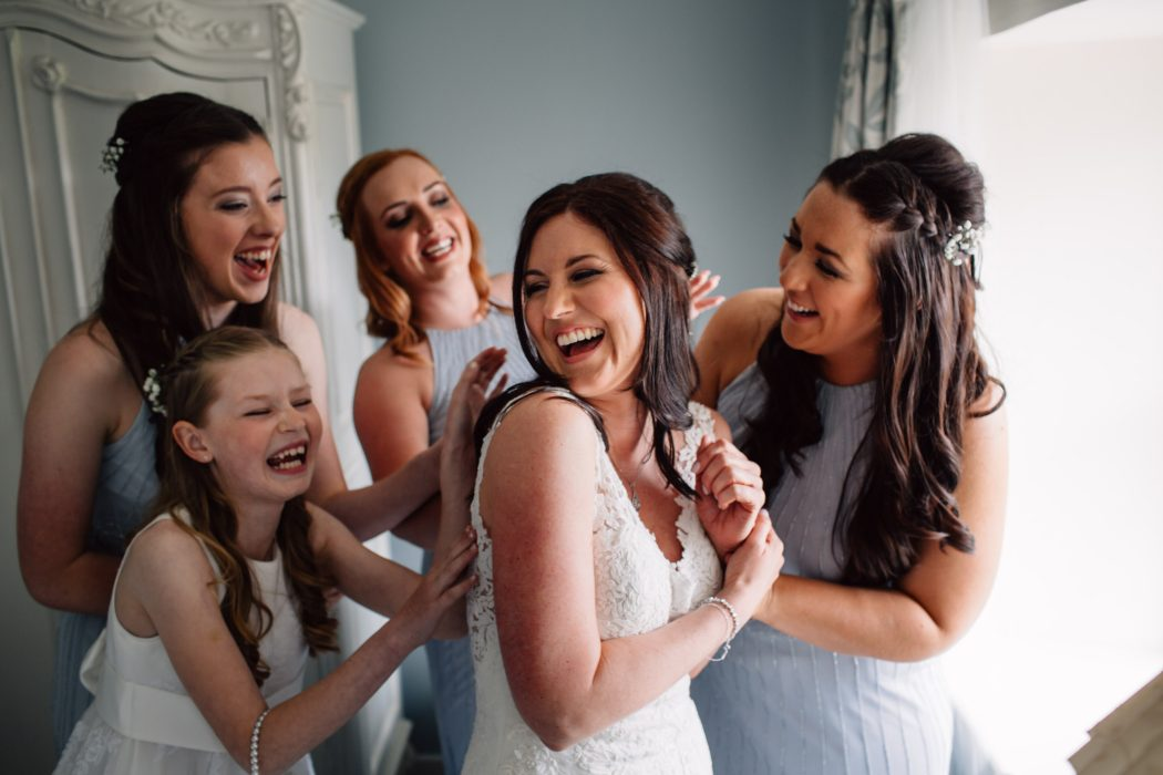 bridesmaids huddle around bride laughing
