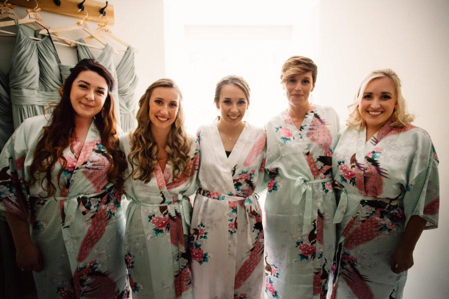 bridesmaids and bride smiling at camera