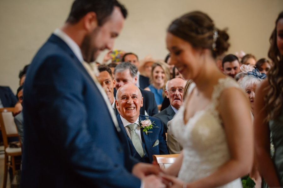 guest watches bride and groom join hands