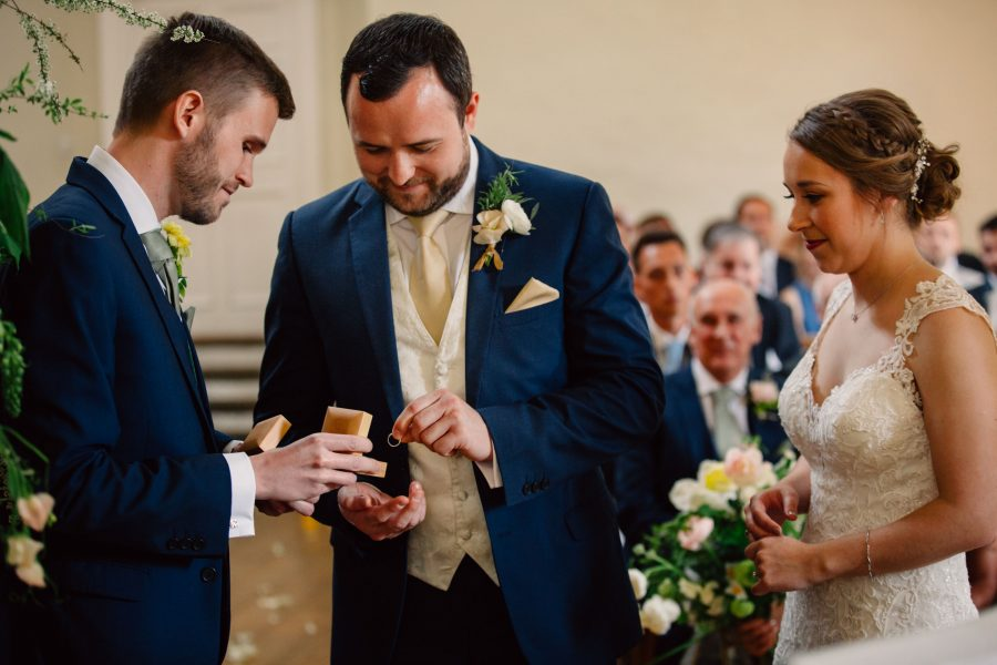 best man hands rings to groom