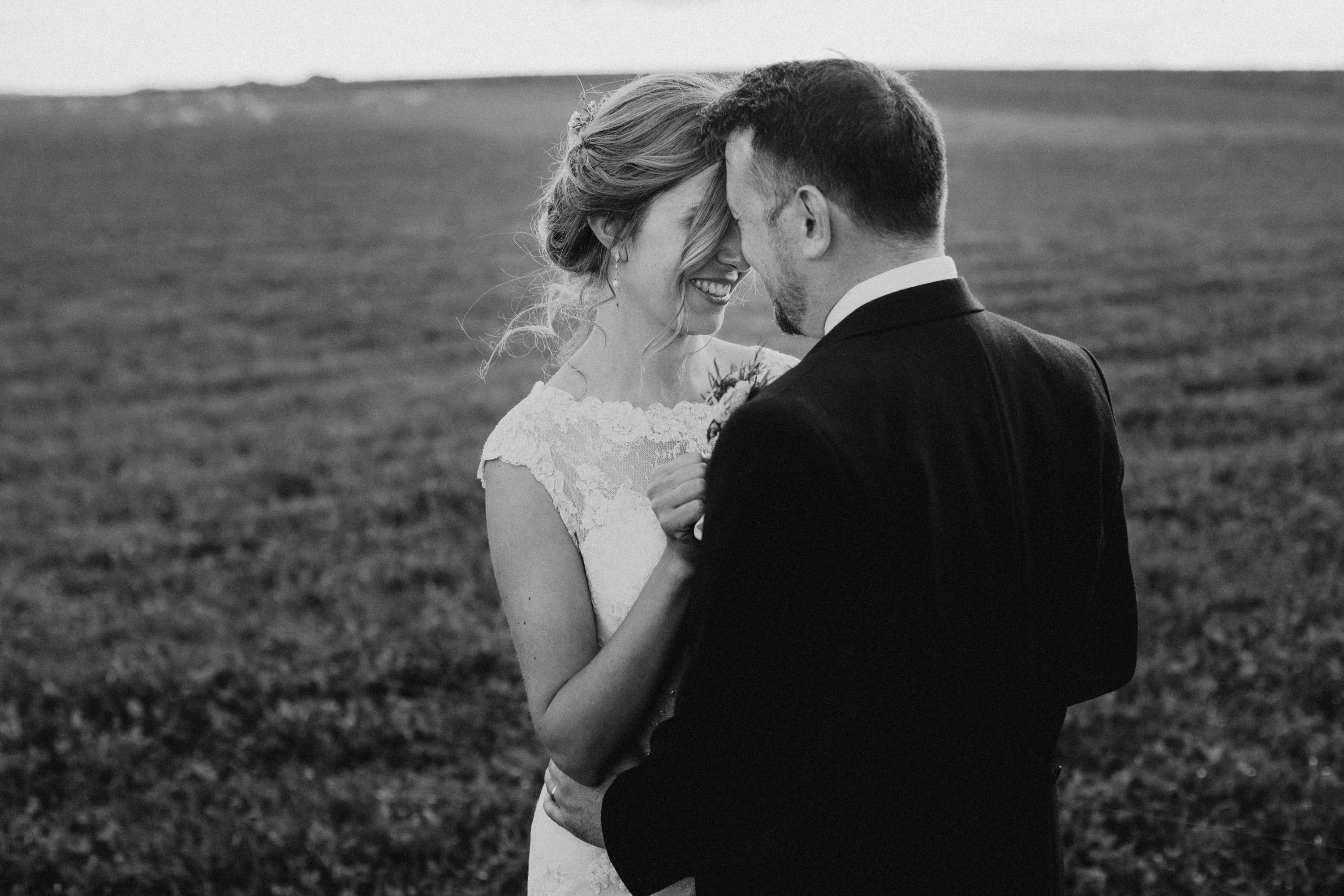 newly weds laughing at sunset