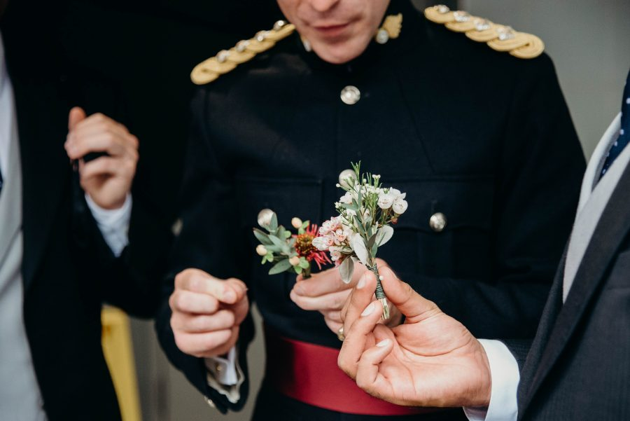 groom doing his buttonhole at the tower of london