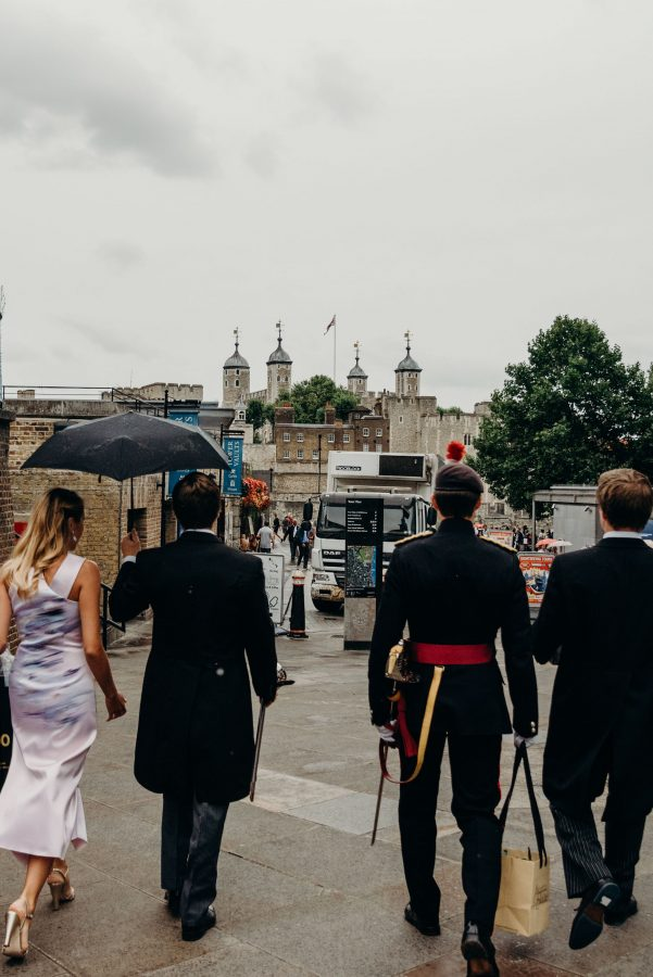 groom walking with his groomsmen to the tower of london for his wedding