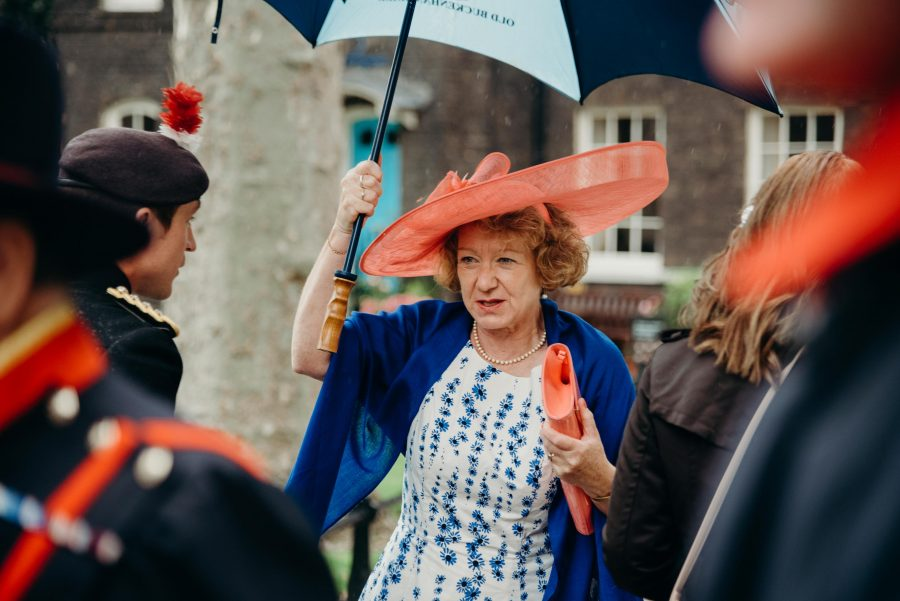 wedding guests arriving at the tower of london in the rain