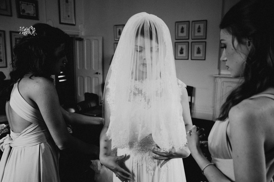 bride behind her veil in black and white during bridal prep
