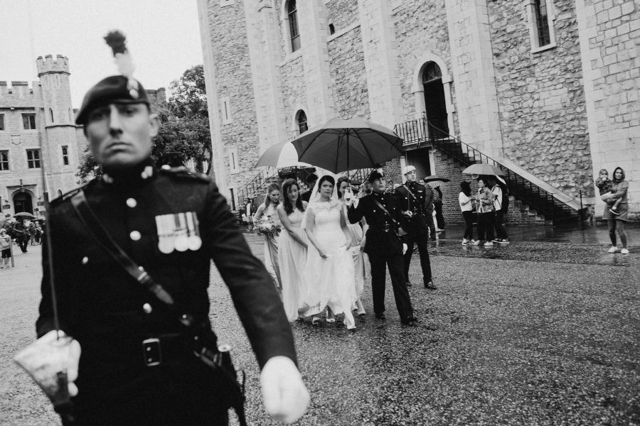 bride being escorted to her wedding at the tower of london by the honour guard in the rain