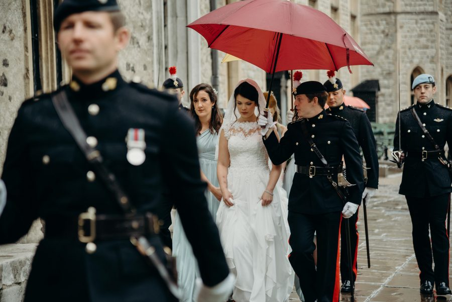 Bride arriving for her wedding at the tower of london in the rain