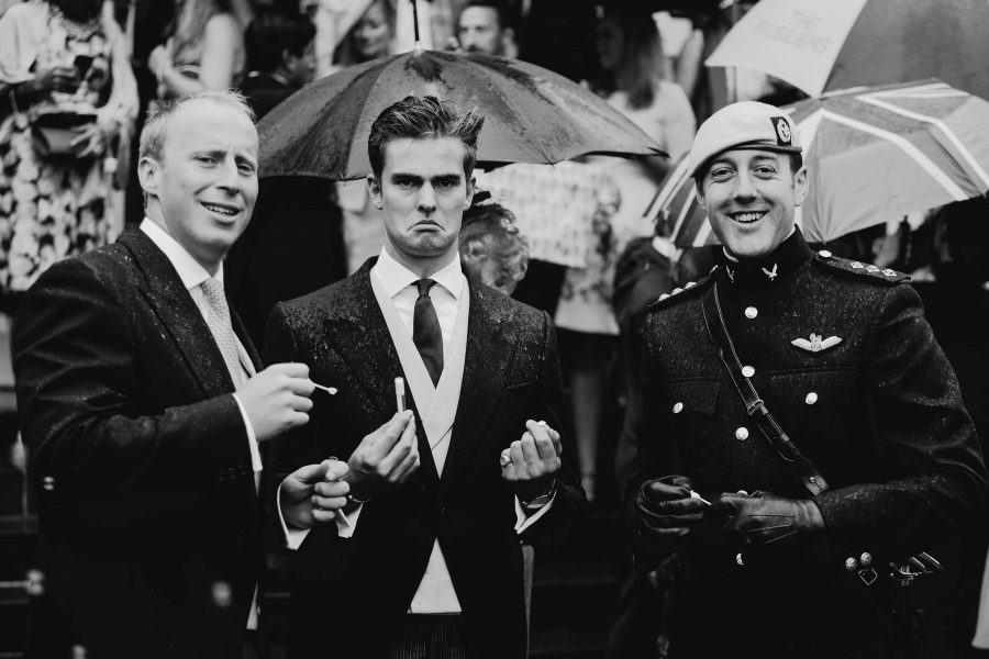 Groomsmen scowling in the rain at the tower of london
