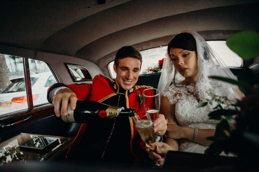 Bridal Couple having champagne in the car on the way to the reception