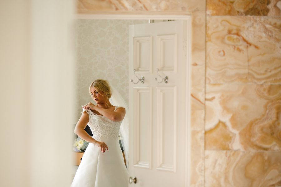 bride putting on wedding dress in doorway