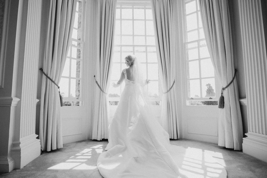 bride looking out of window in Hedsor House bridal suite