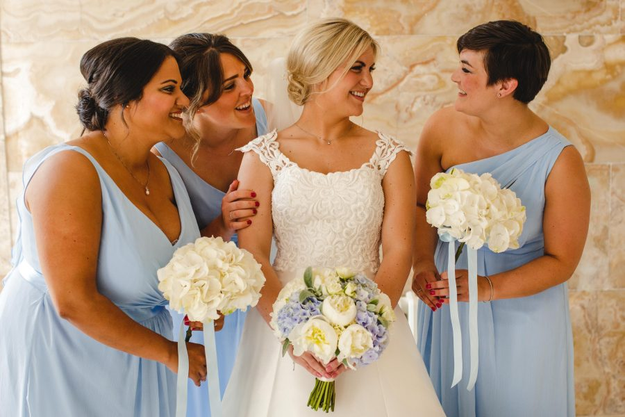 bride and bridesmaids posing ready to leave for church