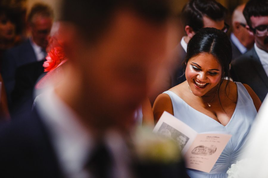 bridesmaid smiling reading service in church