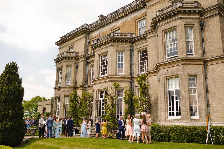wedding party relaxing in the sun outside Hedsor House