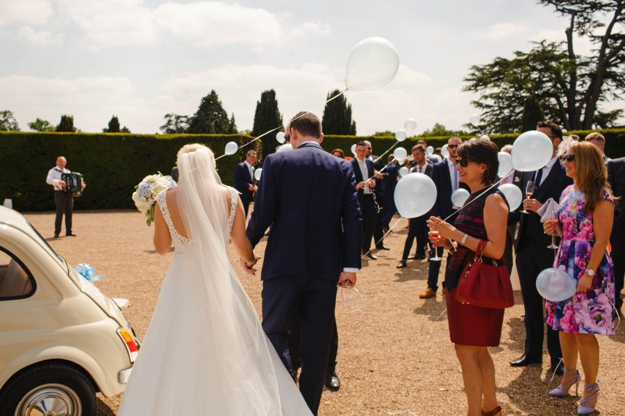 Bride and Groom with balloons outside Hedsor House