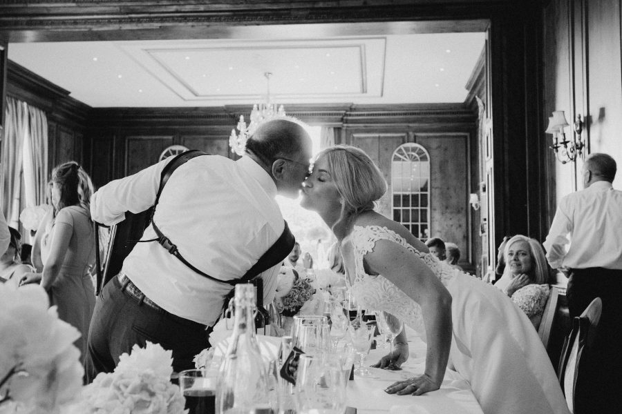 bride kissing accordion singer on cheek at wedding breakfast at Hedsor House
