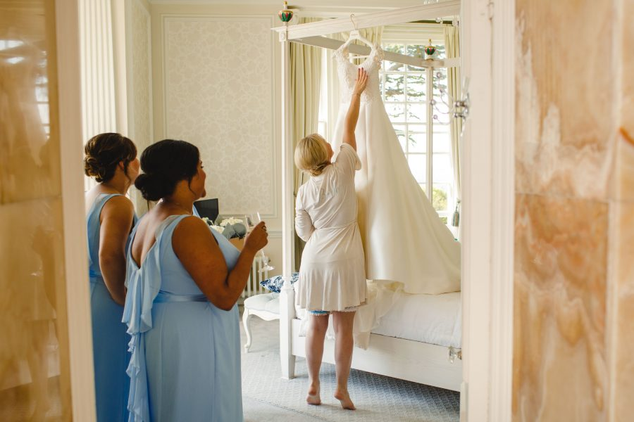 bride reaching for her wedding dress while bridesmaids watch