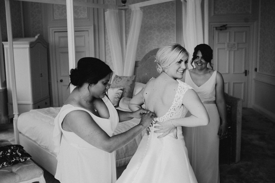 bridesmaids helping zip bride into wedding dress