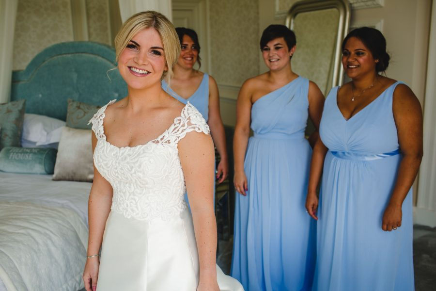 bride beaming and bridesmaids watching after getting ready