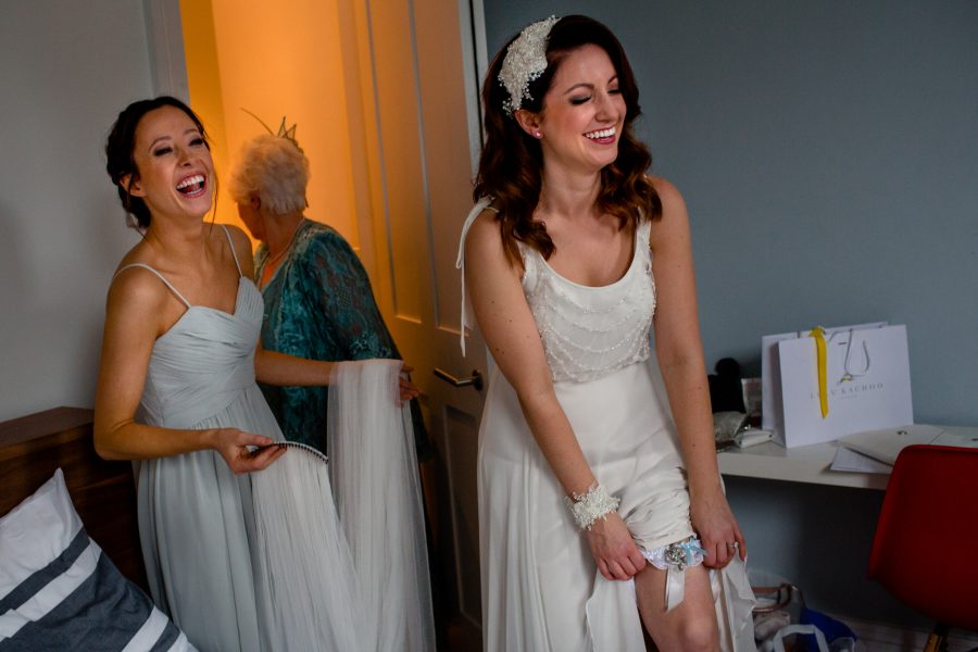 bride showing garter and laughing