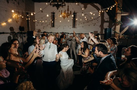 Couple dancing madly at their wedding with all their guests