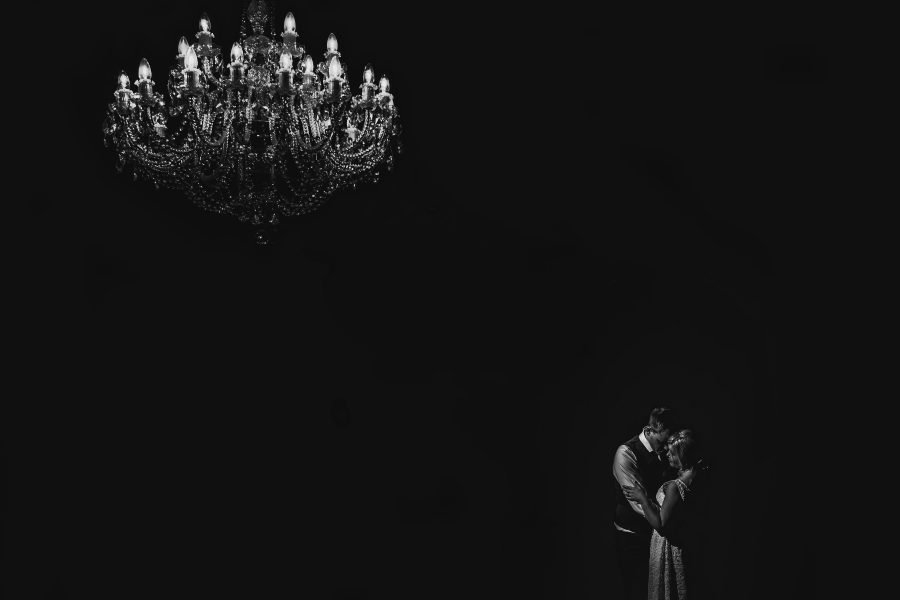 Evening portrait of couple at Botleys Mansion under chandelier