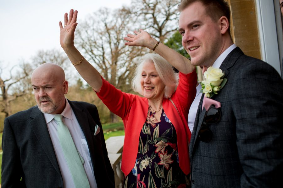 mother of groom waving to guests