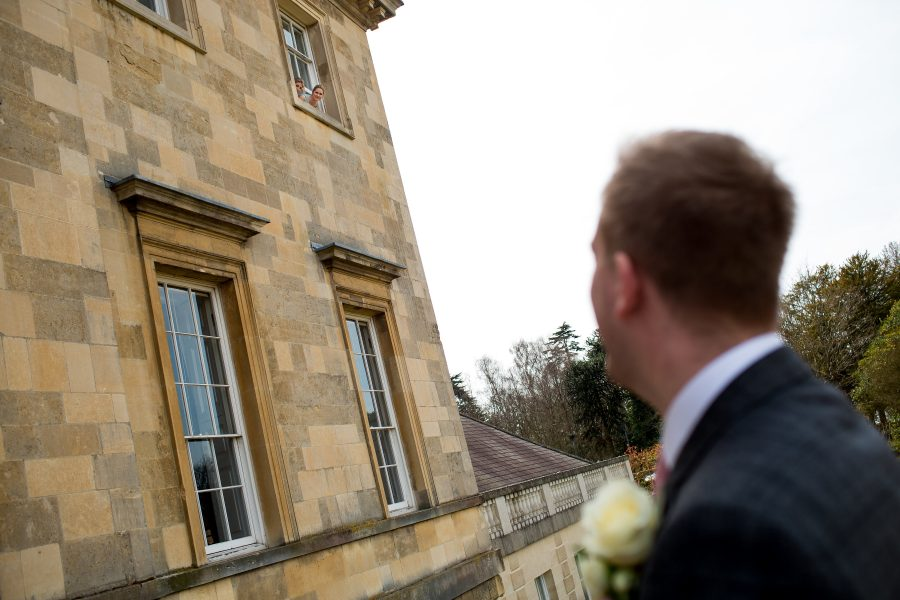Groom shouting up to bridesmaids inside botleys mansion