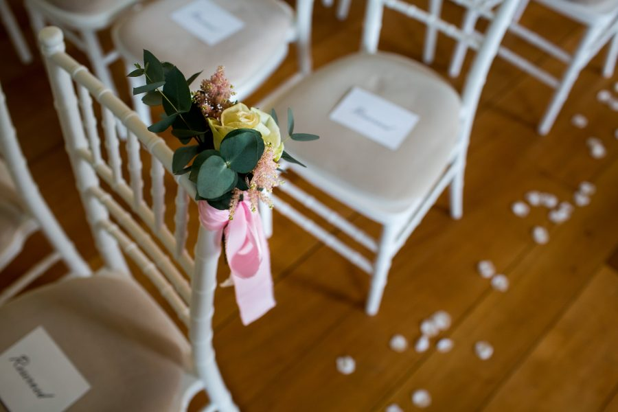 Flowers on chairs in ceremony room