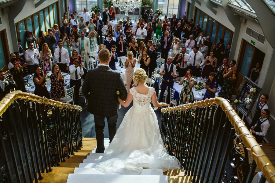 bride and groom descending staircase at Botleys mansion