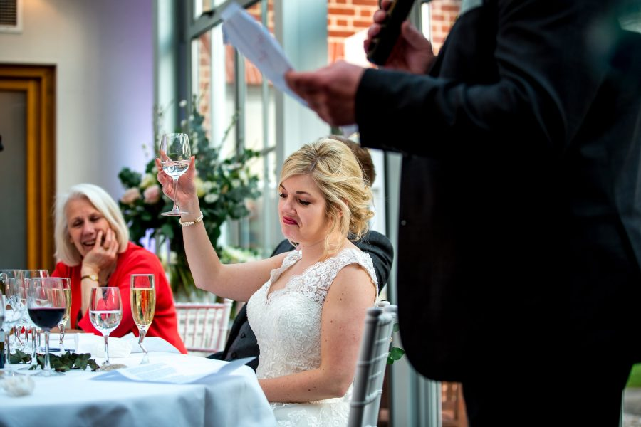 bride acknowledging and raising a glass during speeches