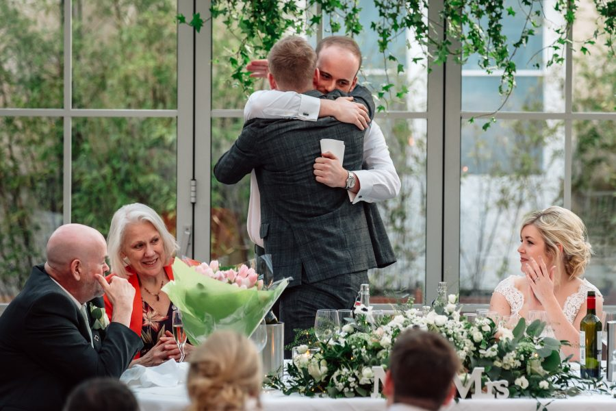 groom and best man hugging after wedding speeches