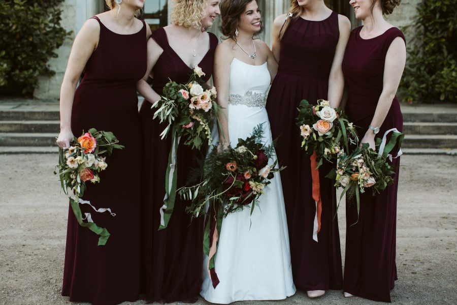 bride and bridesmaids posing with flowers
