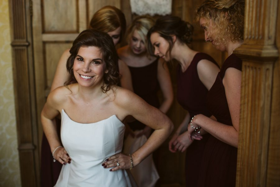 bridesmaids helping bride into her wedding dress