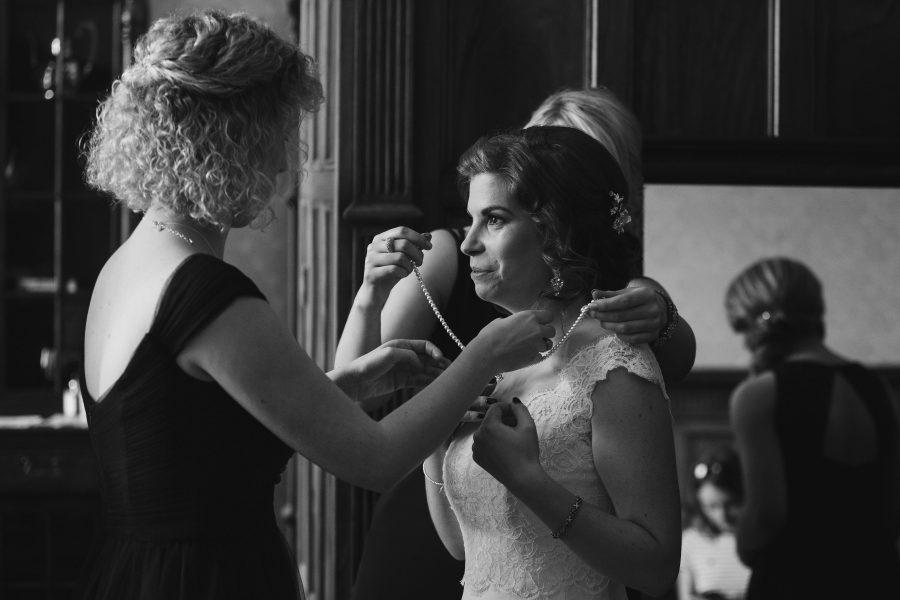 bride putting on wedding jewellery