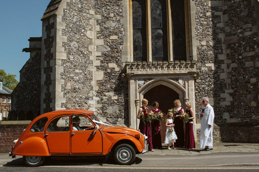 bridal party arriving at church in bright orange Citroen