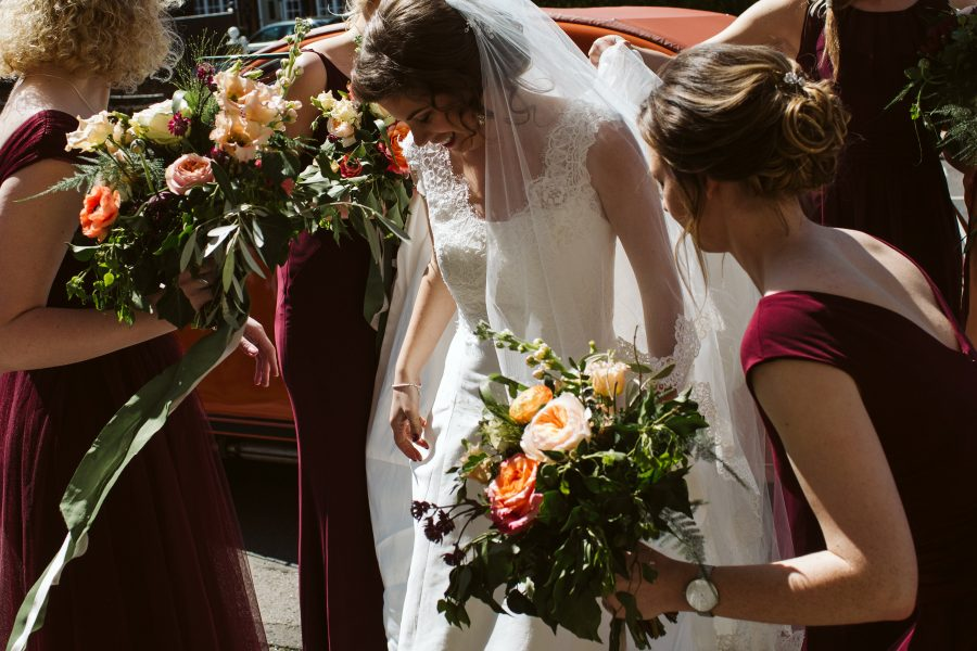 bride surrounded by bridesmaids outside church
