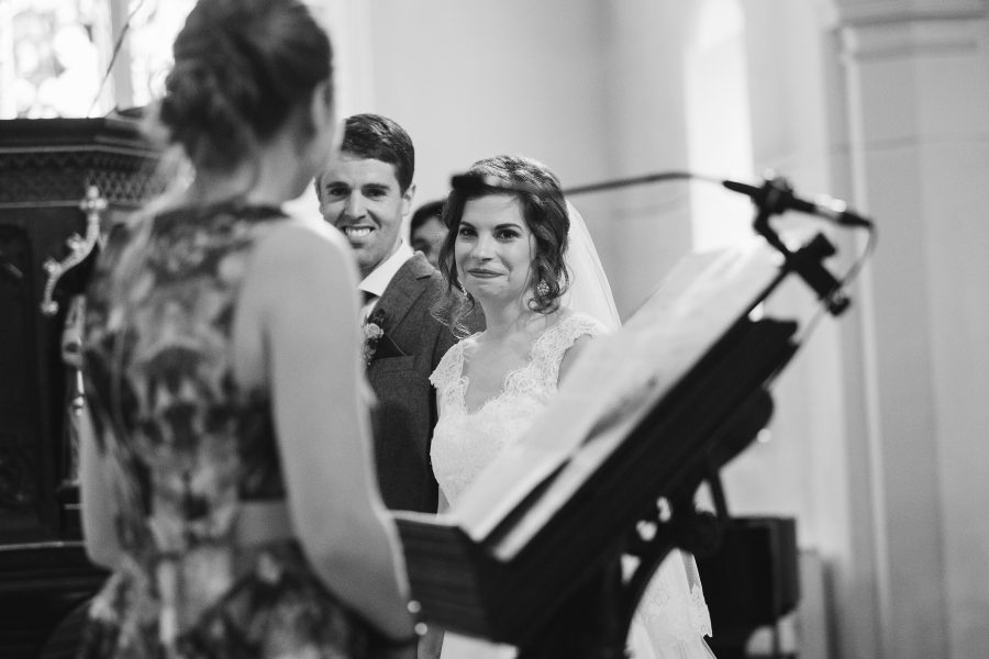 bride smiling at friend reading lesson at wedding
