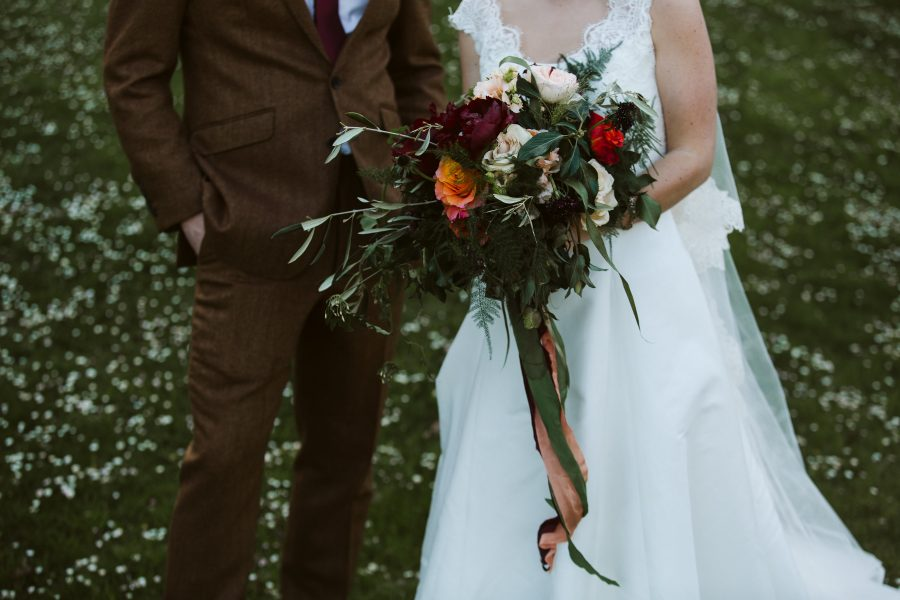 close up of bridal flowers in couples' portrait