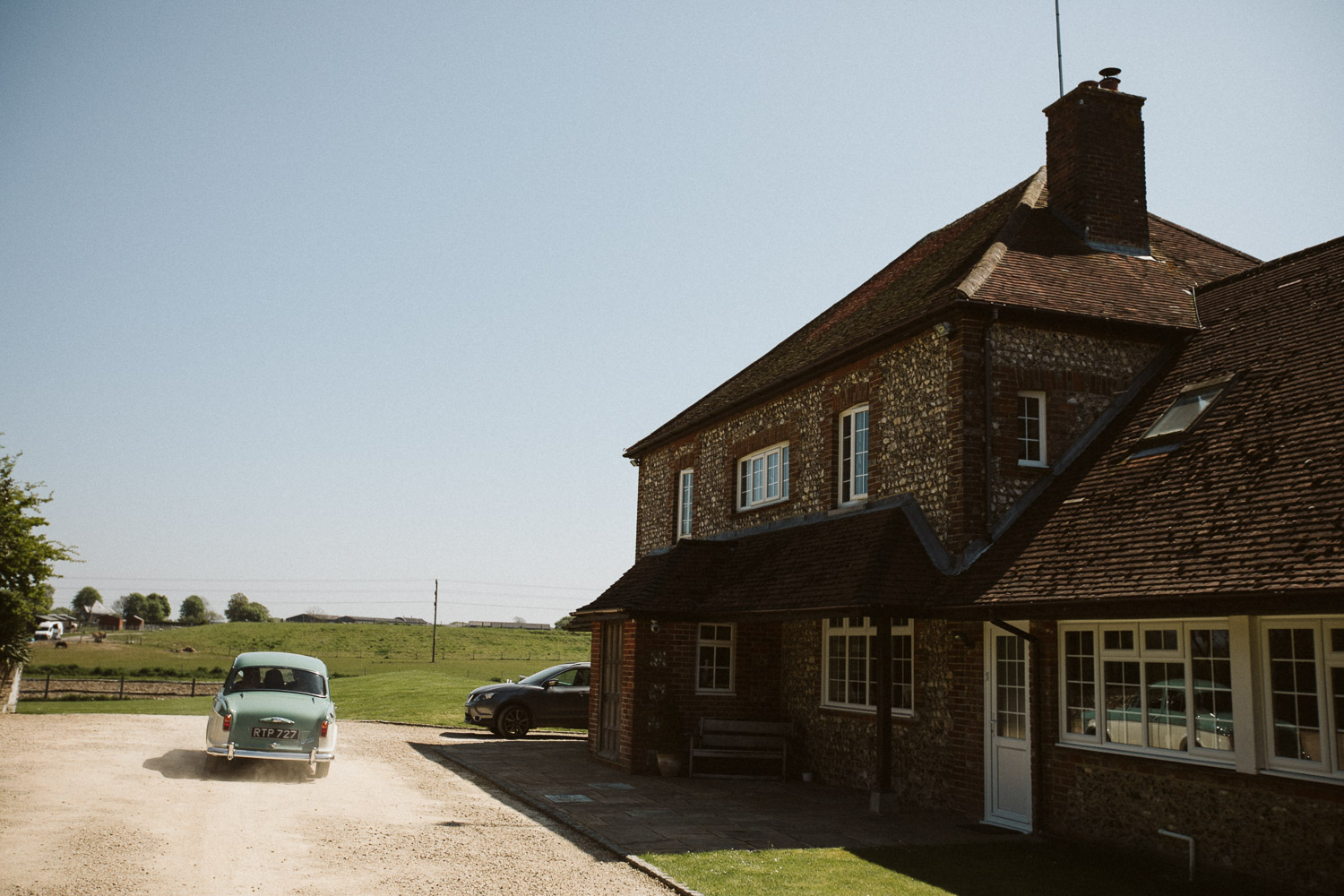 groom and friends leave the house in a vintage car wide angle