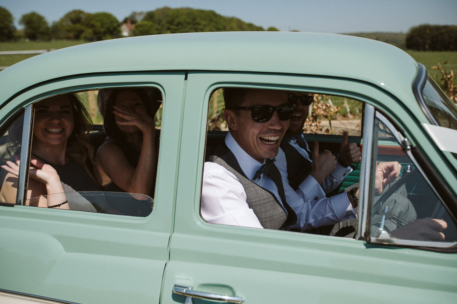 groom and friends squeezed into the vintage car laughing