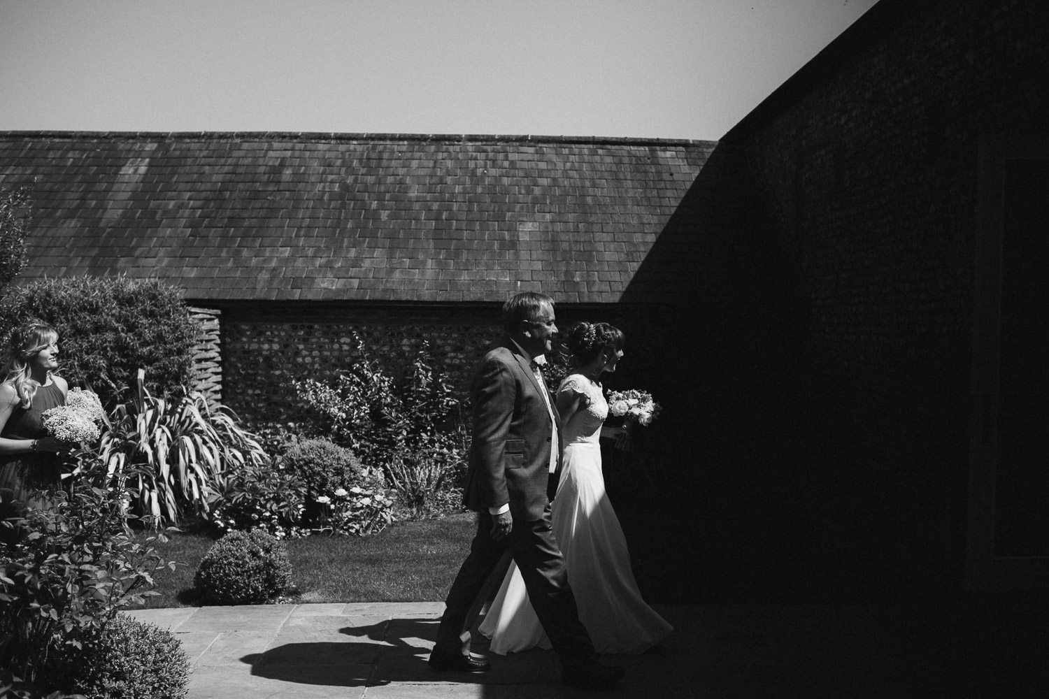 father and bride walking in front of shadows creative