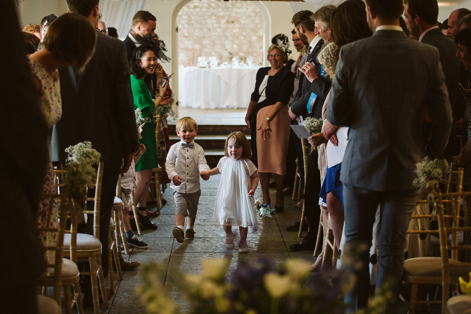 cute page boy and flower girl enter ceremony long lens