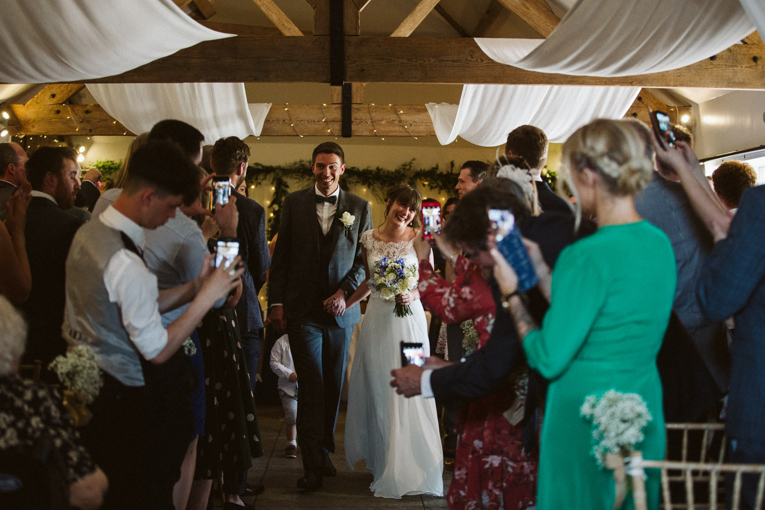 newlyweds walking out of ceremony room lots by mobile phones