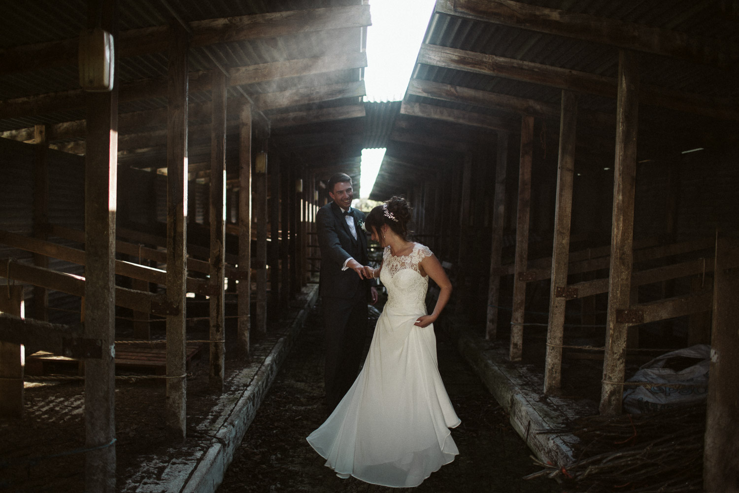 newlyweds helping each other through dusty cowshed