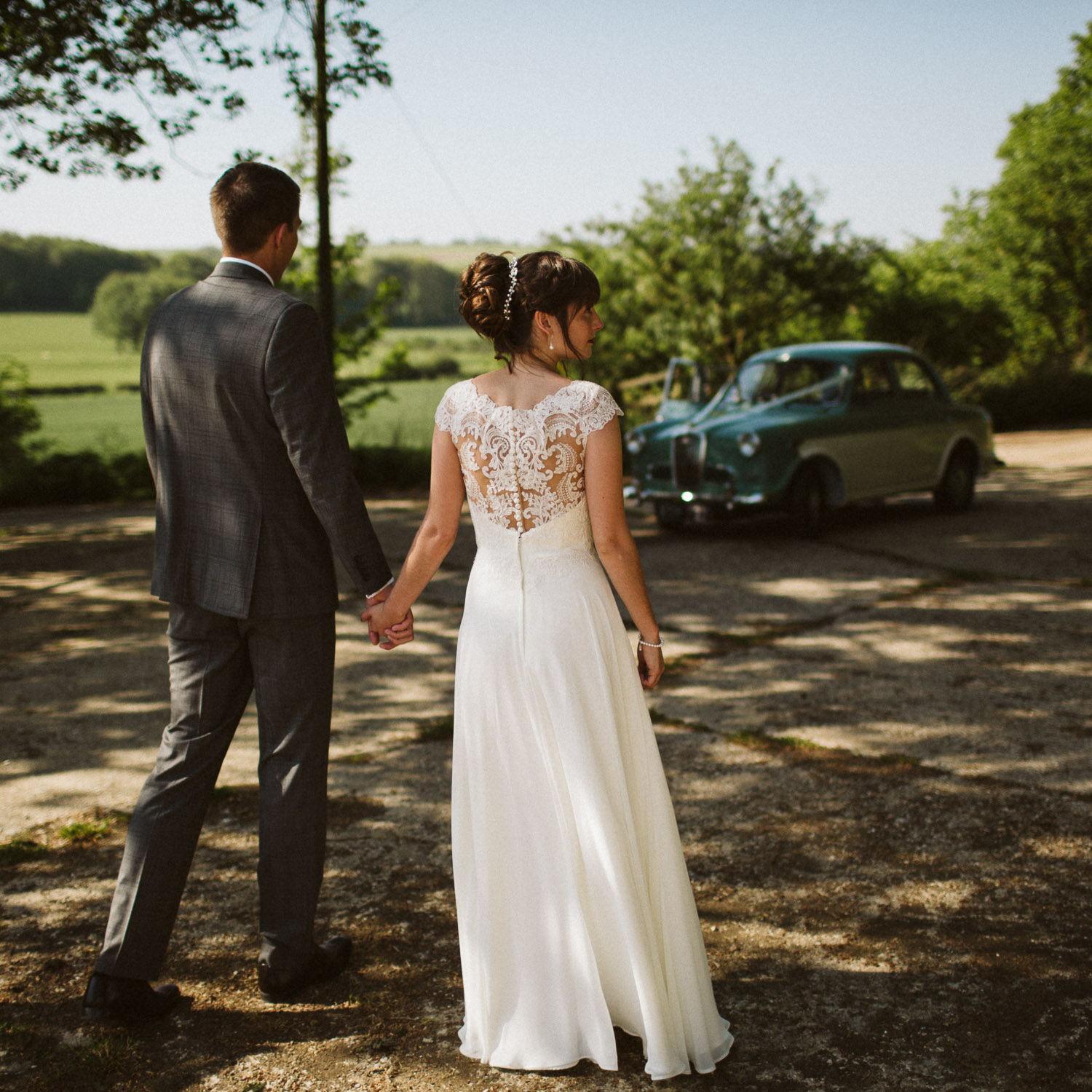 bride and groom from behind with vintage car