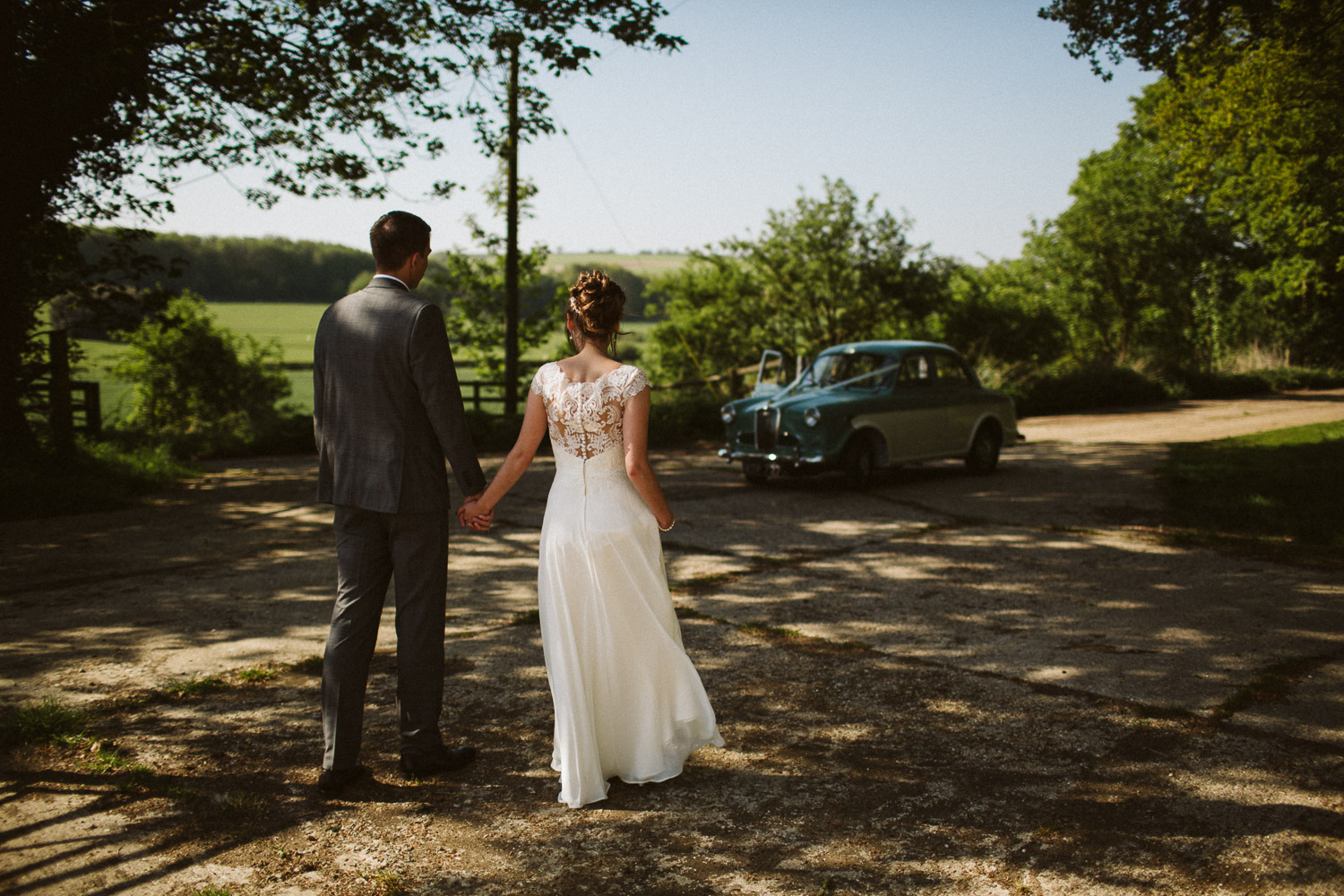 newly weds and vintage car from behind