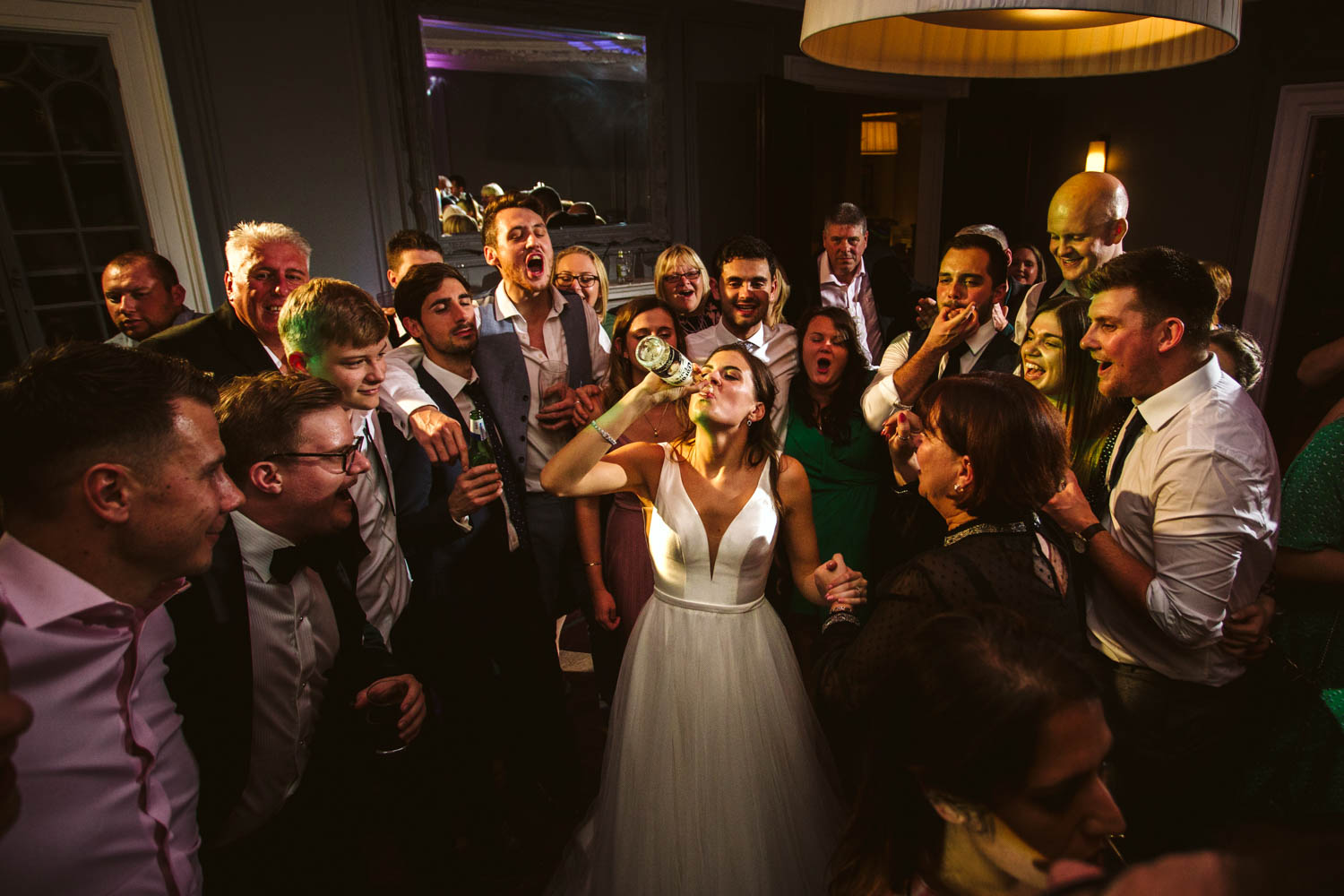beautiful bride downing a bottle of beer while being cheered