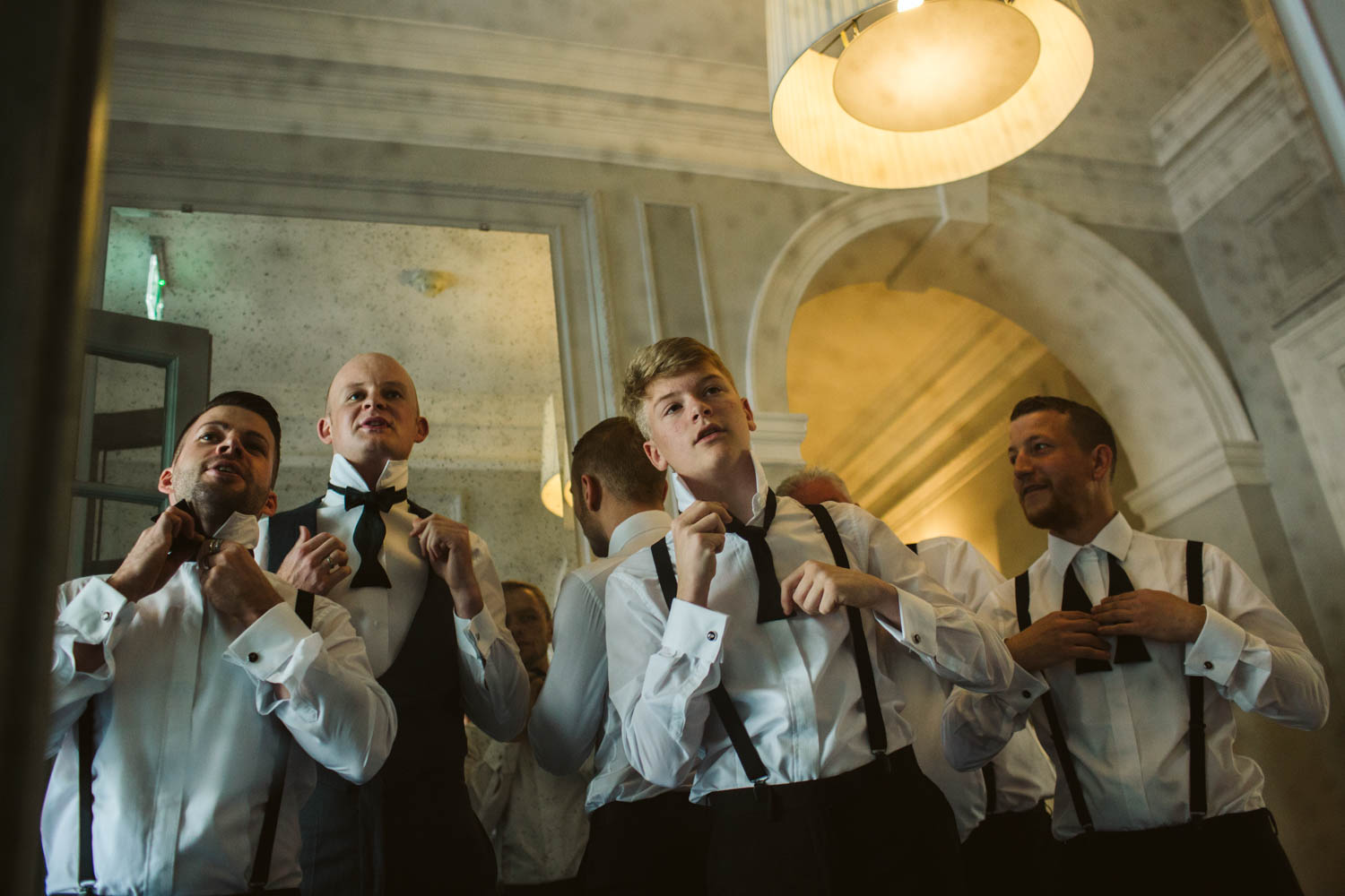 the groomsmen tiring bowties in a funky mirror