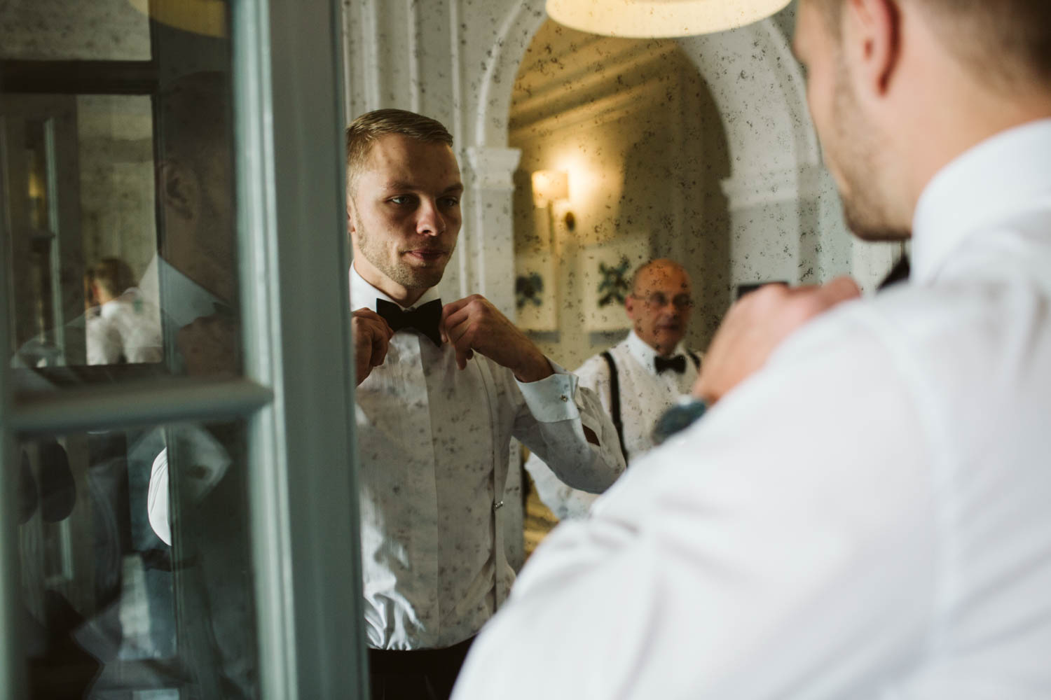 creative portrait of the groom while tying his bowtie